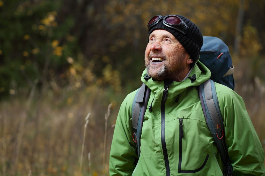 A happy older man hiking through the woods and smiling